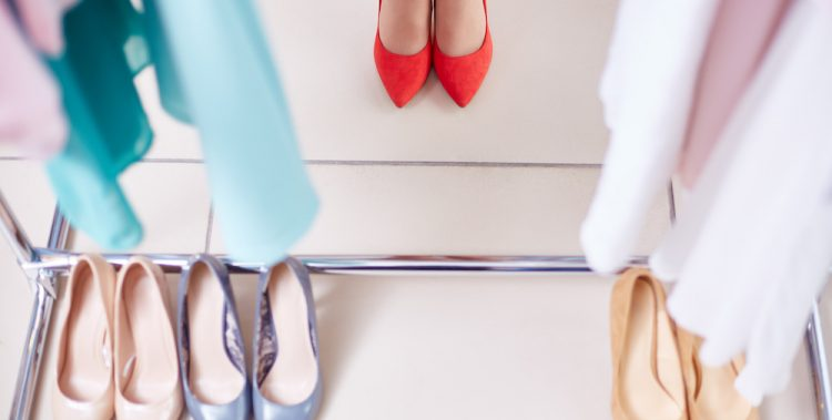 Row of stylish shoes and female feet in red ones