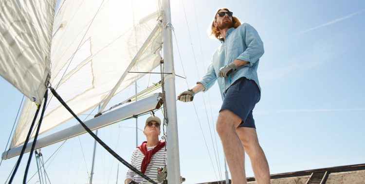 Small group of active men unfolding sails while preparing yacht for journey in the sea