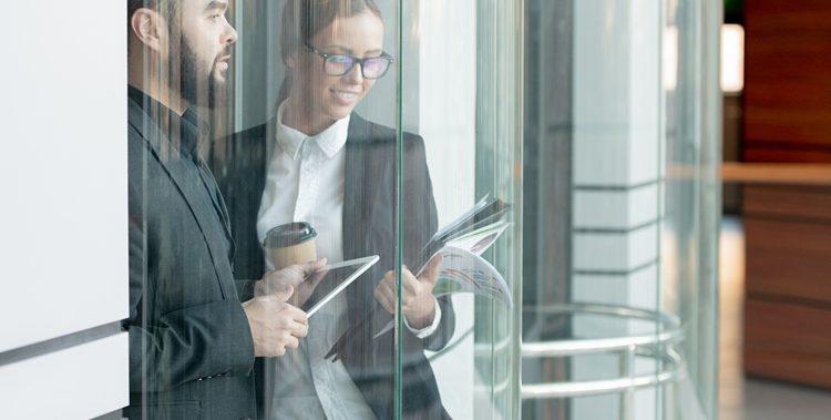 Contemporary office employees in formalwear standing in glassy elevator and checking information on tablet and papers